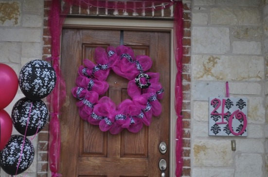 "Hot pink tulle with lights, a hot pink wreath on the door, and a painted canvas ""40"" welcomed guests."