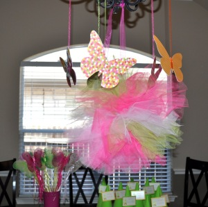 Butterflies and a tulle poof hanging from the chandelier